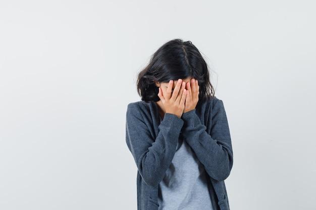 Klein meisje in t-shirt, jasje dat gezicht bedekt met handen en depressief, vooraanzicht kijkt.