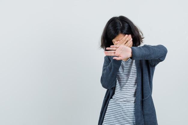 Klein meisje in t-shirt, jasje dat gezicht bedekt, stopgebaar toont en boos kijkt,