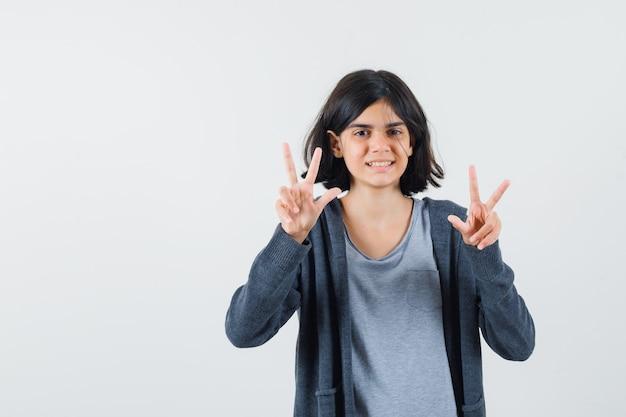 Klein meisje in t-shirt, jasje dat ik hou van je gebaar laat zien en er vrolijk uitziet