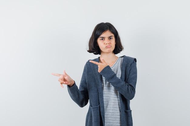 Klein meisje in t-shirt, jasje dat opzij wijst en twijfelachtig kijkt