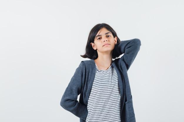 Klein meisje in t-shirt, jasje hand op de nek houden en er ontspannen uitzien