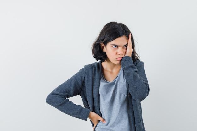 Klein meisje in t-shirt, jasje hand op het hoofd houden en hulpeloos, vooraanzicht op zoek.