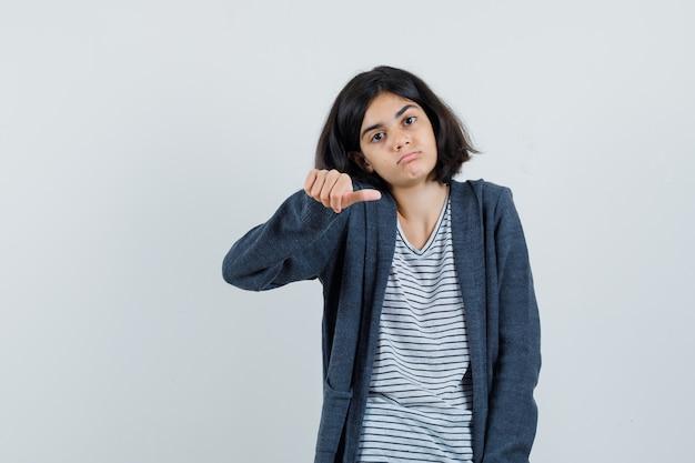 Klein meisje in t-shirt, jasje met duim midden en op zoek verdrietig,