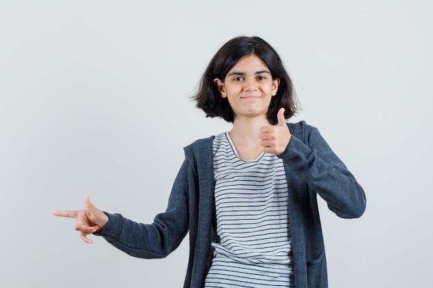 Klein meisje in t-shirt, jasje met duim omhoog, opzij wijzend en er vrolijk uitziend,