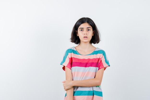 Klein meisje in t-shirt, jeans die hand op arm houdt en verrast kijkt, vooraanzicht.