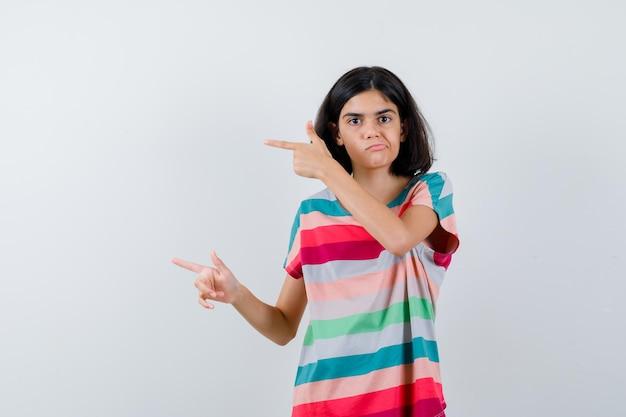Klein meisje in t-shirt, jeans die met wijsvingers naar links wijst en er ontevreden uitziet, vooraanzicht.