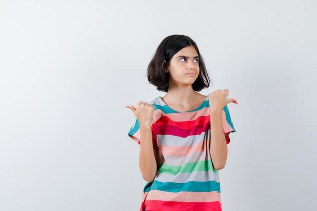 Klein meisje in t-shirt, jeans die naar links en rechts wijst en er ontevreden uitziet, vooraanzicht.