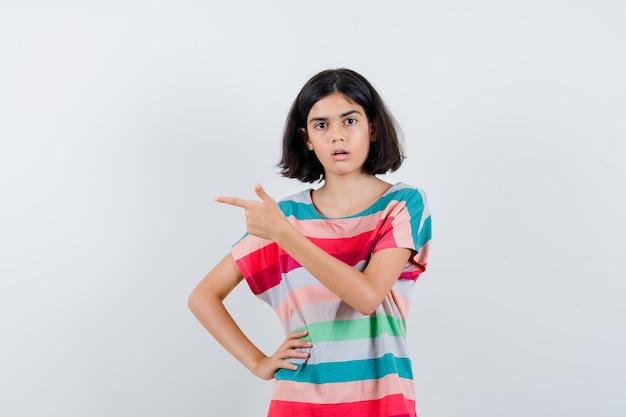 Klein meisje in t-shirt, jeans die naar links wijst terwijl ze de hand op de taille houdt en verrast kijkt, vooraanzicht.