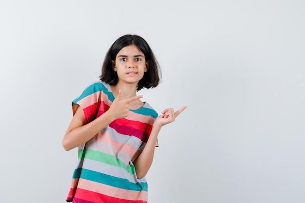 Klein meisje in t-shirt, jeans die naar rechts wijst met wijsvingers en er gelukkig uitziet, vooraanzicht.