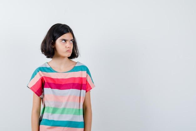 Klein meisje in t-shirt, jeans die wegkijkt terwijl ze de tong uitsteekt en er geamuseerd uitziet, vooraanzicht.