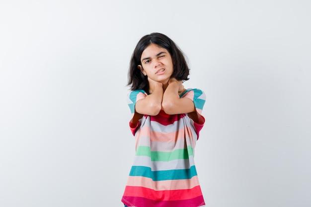 Klein meisje in t-shirt, jeans hand in hand op nek, nekpijn hebben en er uitgeput uitzien, vooraanzicht.