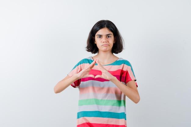 Klein meisje in t-shirt, jeans met verzekeringsgebaar en ontevreden, vooraanzicht.