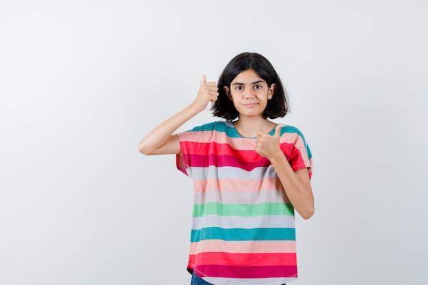 Klein meisje in t-shirt met dubbele duimen omhoog en ziet er gelukkig uit, vooraanzicht.
