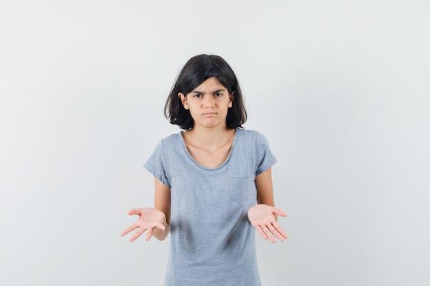 Klein meisje in t-shirt met hulpeloos gebaar en op zoek naar verward, vooraanzicht.