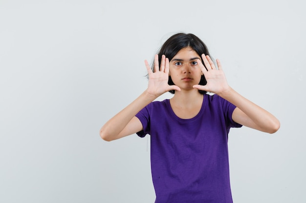 Klein meisje in t-shirt met stop gebaar en ziet er moe uit,