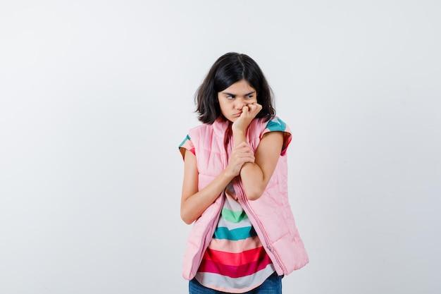 Klein meisje in t-shirt, puffer vest, jeans leunend op de hand als kussen en weemoedig kijken, vooraanzicht.