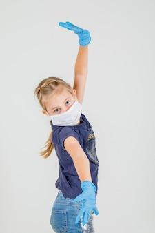 Klein meisje in t-shirt, rok en masker met groot formaat teken met handen