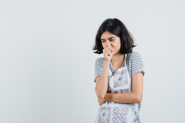 Klein meisje in t-shirt, schort die aan hoest lijdt en boos kijkt,