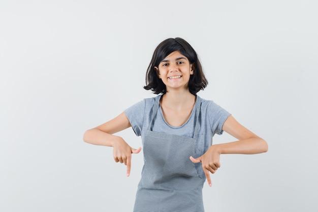 Klein meisje in t-shirt, schort die naar beneden wijst en er vrolijk uitziet, vooraanzicht.