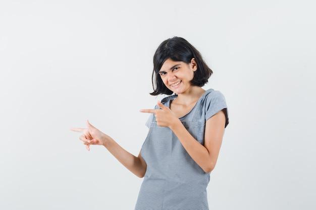Klein meisje in t-shirt, schort die opzij wijst en er vrolijk uitziet, vooraanzicht.