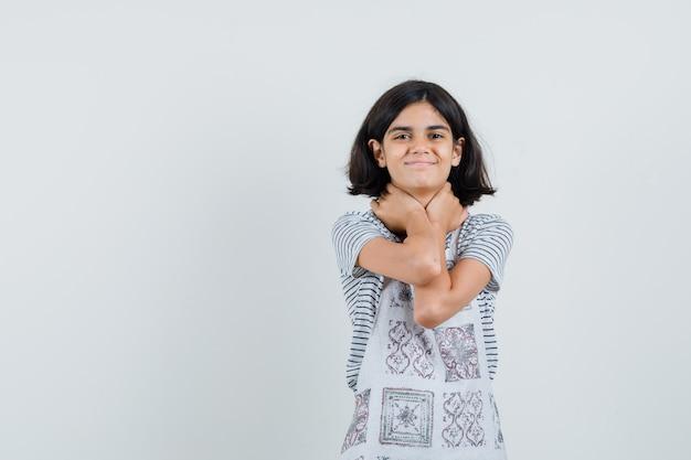 Klein meisje in t-shirt, schort hand in hand op nek en vrolijk op zoek,