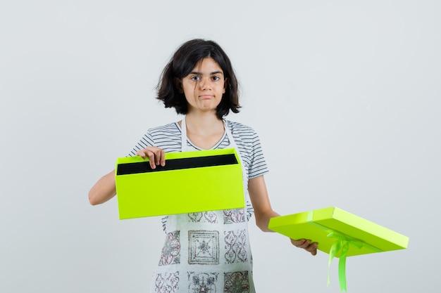 Klein meisje in t-shirt, schort met geopende huidige doos en kijkt verward,