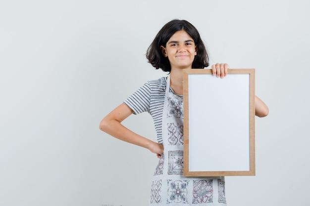 Klein meisje in t-shirt, schort met wit frame en ziet er vrolijk uit,