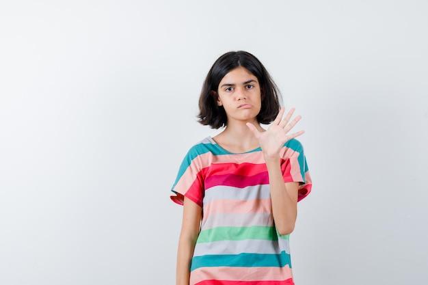 Klein meisje in t-shirt, spijkerbroek die hand opsteekt om iemand te begroeten, lippen gebogen en er ontevreden uit te zien, vooraanzicht.