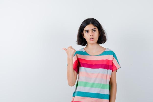 Klein meisje in t-shirt, spijkerbroek met duim omhoog en verbaasd, vooraanzicht.