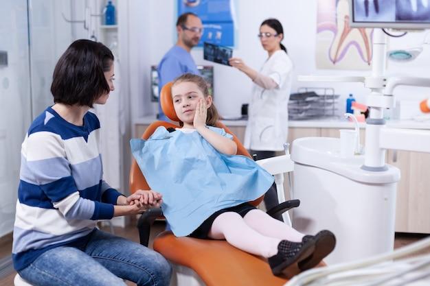 Klein meisje in tandartspraktijk die ouder toont waar tand pijn doet bij het aanraken van gezicht met pijnlijke uitdrukking. kind met haar moeder tijdens tandencontrole met stomatolog zittend op een stoel.