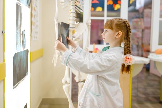 Klein meisje in uniform kijkt naar de röntgenfoto,