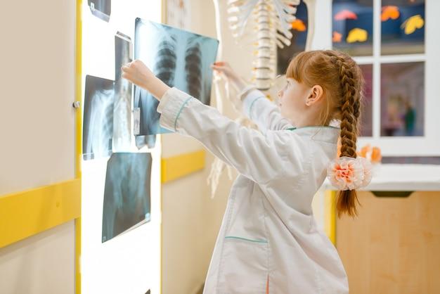 Klein meisje in uniform kijkt naar de x-ray, dokter