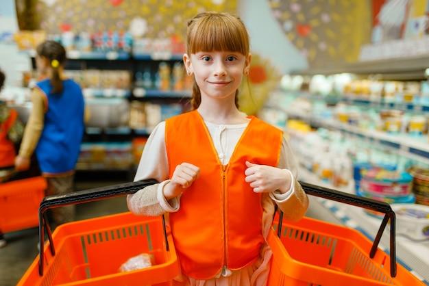 Klein meisje in uniform met manden in handen verkoopster spelen