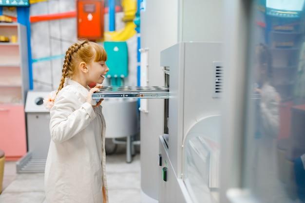 Klein meisje in uniform spelen arts in analyselaboratorium