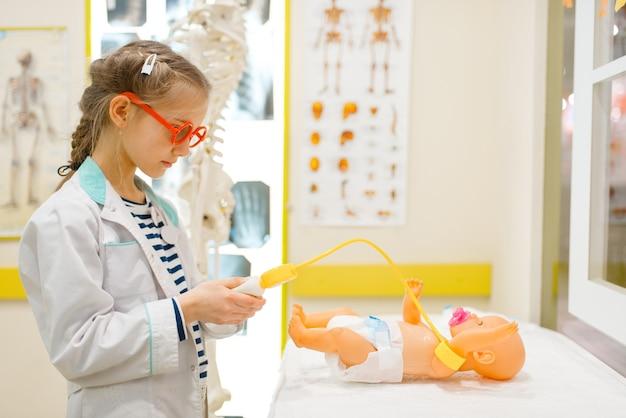Klein meisje in uniform spelen arts met pop