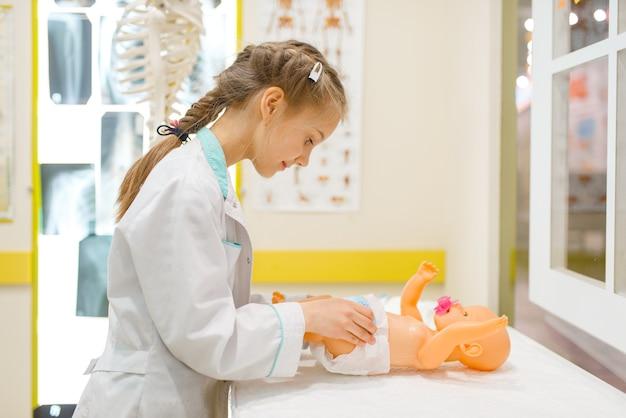 Klein meisje in uniform spelen arts met speelgoedpop