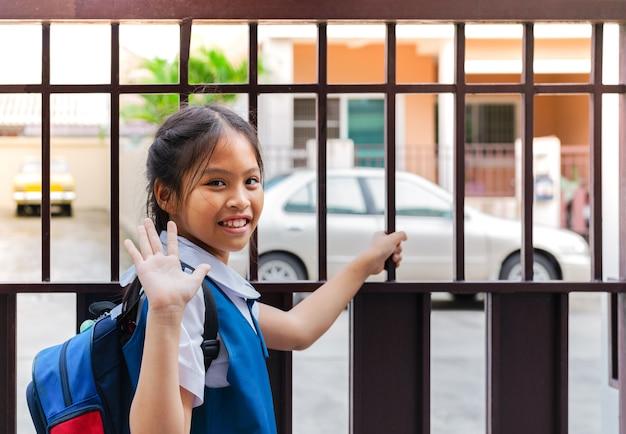 Klein meisje in uniform zeg vaarwel voor vertrek naar school in de ochtend met blauwe rug