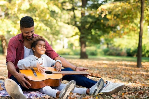 Klein meisje in vaders omhelzing leren gitaar spelen