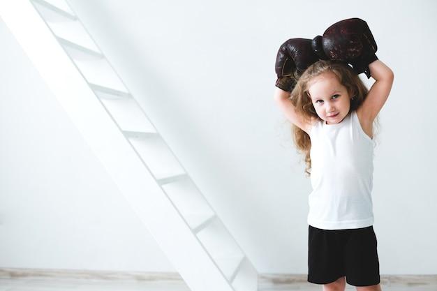 Klein meisje in vintage bokshandschoenen. dromer.