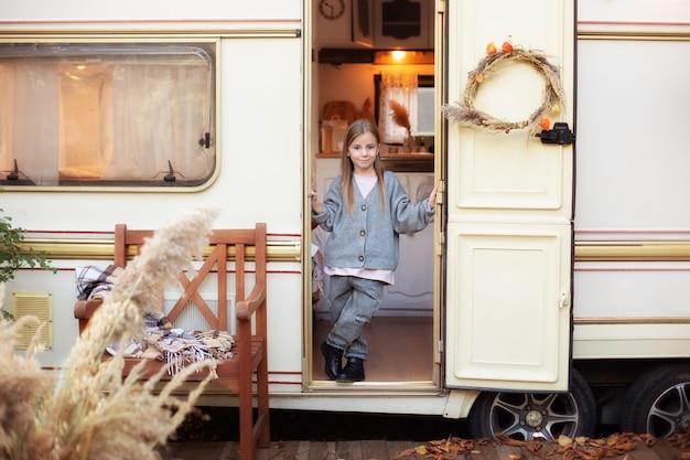 Klein meisje in vrijetijdskleding in de buurt van camping met trailerdeur op veranda rv-huis in tuin