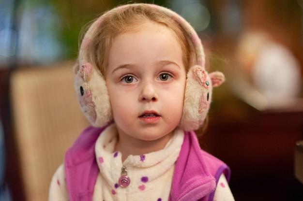 Klein meisje in warme hoofdtelefoons