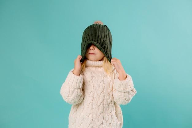 Klein meisje in winter muts en trui op blauw