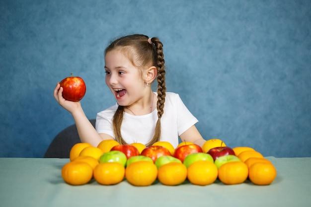 Klein meisje in wit t-shirt houdt van fruit