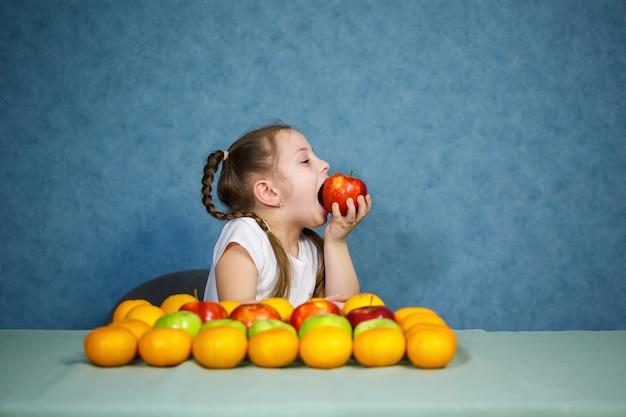 Klein meisje in wit t-shirt houdt van fruit Premium Foto
