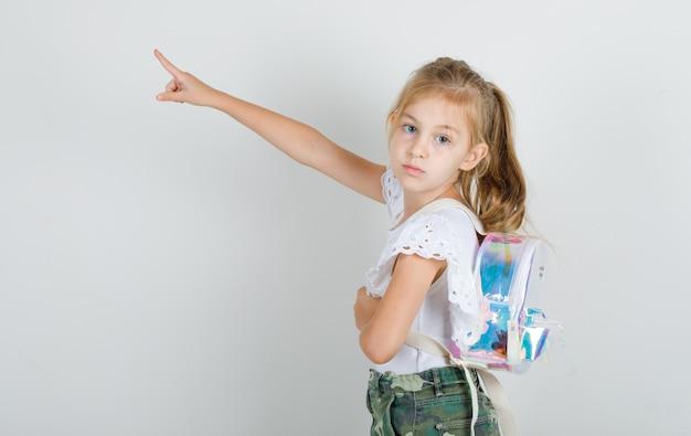 Klein meisje in wit t-shirt, rok die weg wijst met rugzak