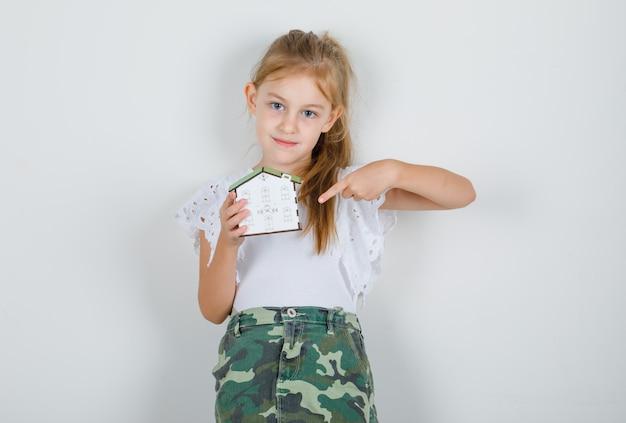 Klein meisje in wit t-shirt, rok wijzende vinger naar huismodel en hoopvol op zoek