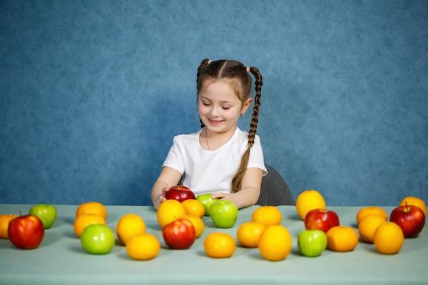 Klein meisje in wit t-shirt speelt en poseert met fruit