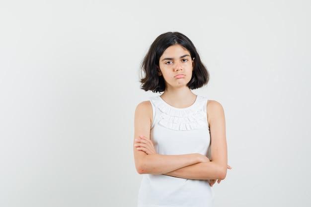 Klein meisje in witte blouse staan met kruisen armen en op zoek boos, vooraanzicht.