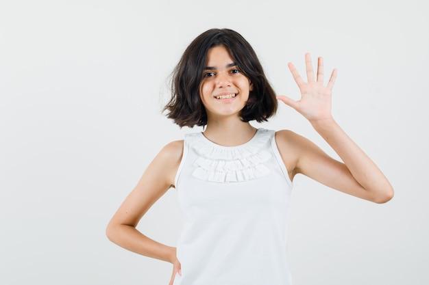 Klein meisje in witte blouse zwaaiende hand om hallo of tot ziens te zeggen en op zoek vrolijk, vooraanzicht.