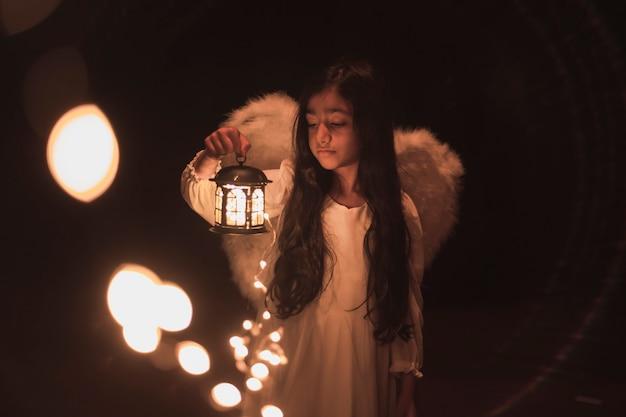 Klein meisje in witte engel jurk met vleugels